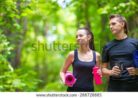 Jogging active couple have a rest with mat and bottle of water outdoors in forest - stock photo