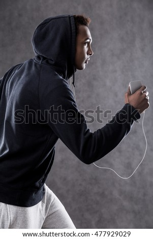 Jogging African American man with black hood on and smartphone in hand. Concept of fitness and health