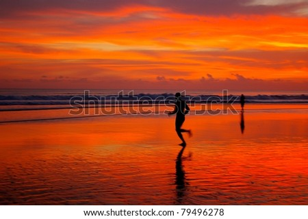 Jogging at sunset, on Double Six beach, Bali, Indonesia. - stock photo