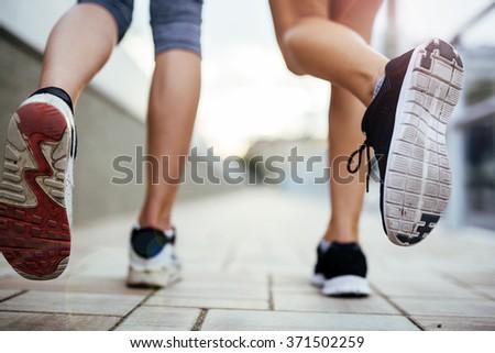 Jogging athletic women - closeup on legs - stock photo