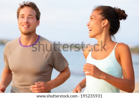 Jogging fitness young mixed race couple running happy smiling and laughing enjoying sports outdoors. Exercising multicultural people - young caucasian man and pretty asian model - stock photo