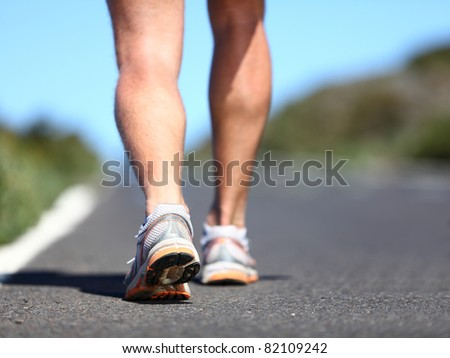 Jogging man. Running shoes and legs of male runner outside on road. - stock photo
