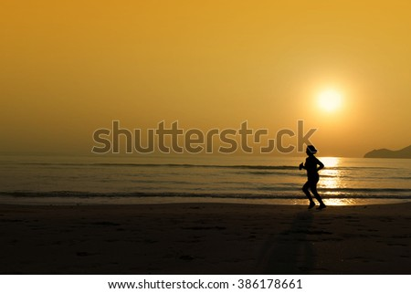 Jogging on the beach seaside during sunrise and orange sky. silhouette concept - stock photo