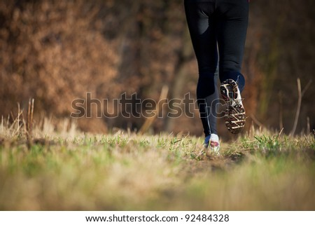 Jogging outdoors in a meadow (shallow dof, focus on the running shoe) - stock photo