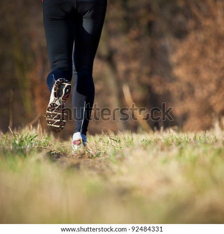 Jogging outdoors in a meadow (shallow dof, focus on the running shoe)
