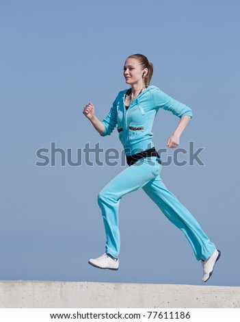 Jogging. Running woman against the blue sky. - stock photo