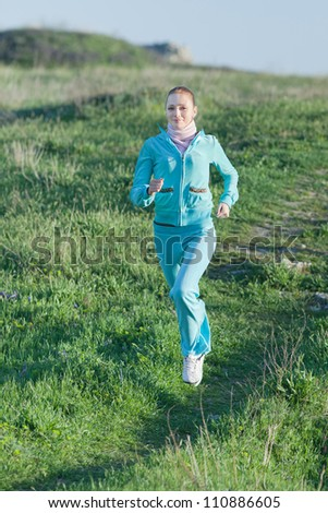 Jogging. Slim girl runs along field