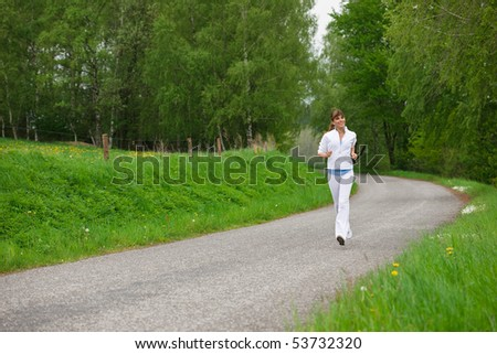 Jogging - sportive woman running on road in nature, listen to music with ear buds