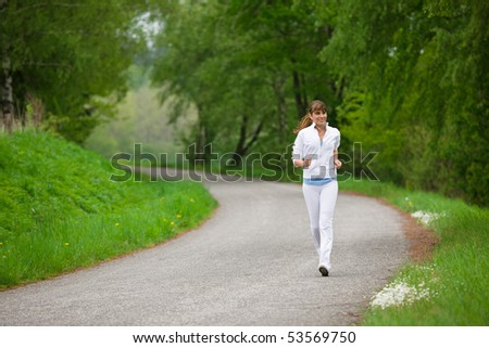 Jogging - sportive woman running on road in nature, listen to music with earbuds