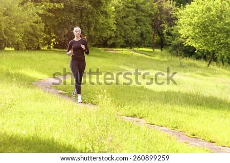 Jogging Theme: Caucasian Sportswoman Having Jogging Exercises Outdoors. Horizontal Image Orientation - stock photo