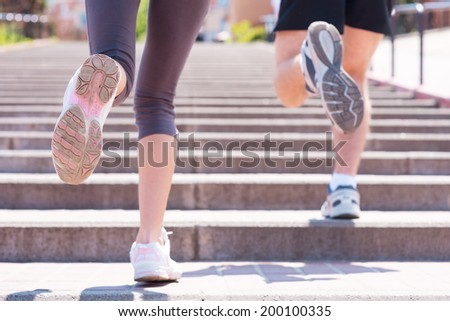 Jogging together.  Rear view of woman and man running along the stairs  - stock photo