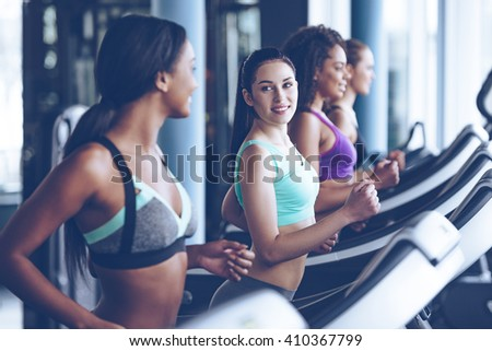 Jogging with pleasure. Side view of young beautiful women looking at each other with smile while running on treadmill at gym  - stock photo