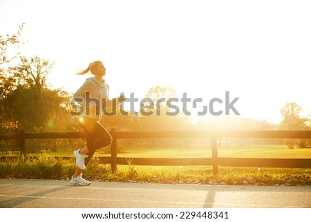 Jogging woman running in park - stock photo