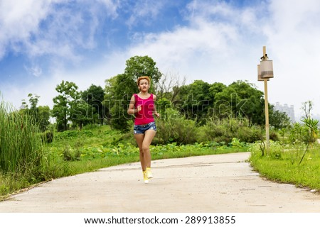 Jogging woman running in park in sunshine on beautiful summer da - stock photo