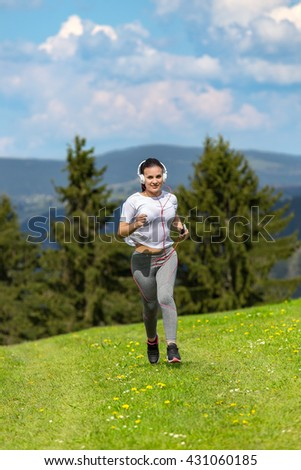 Jogging woman running in sunshine on beautiful summer day and listening a music in headphones. Sport fitness model caucasian ethnicity training outdoor for marathon. - stock photo
