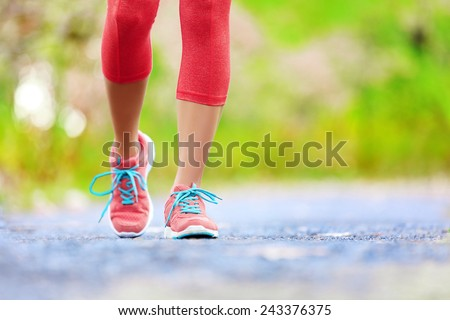 Jogging woman with athletic legs and running shoes. Female walking on trail in forest in healthy lifestyle concept with close up on running shoes. Female athlete jogger training outdoors. - stock photo