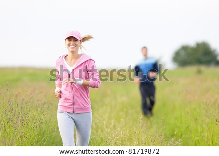 Jogging young fit couple running field meadow in sportswear tracksuit - stock photo