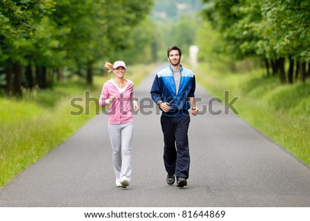 Jogging young fit couple running park road in sportswear tracksuit - stock photo