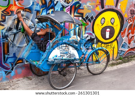 JOGYAKARTA, JAVA - MARCH 16: Trishaw resting in wheelchair on graffiti background,  March 16, 2014 at Jogyakarta, Indonesia. Pedicabs are still the most popular  vehicles in South-East Asia - stock photo