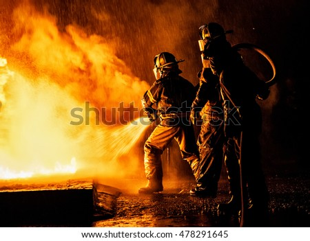 JOHANNESBURG, SOUTH AFRICA - AUGUST 26: Two firefighters fighting a fire with a hose and water during a firefighting training exercise on August 26, 2016 in Johannesburg, South Africa.