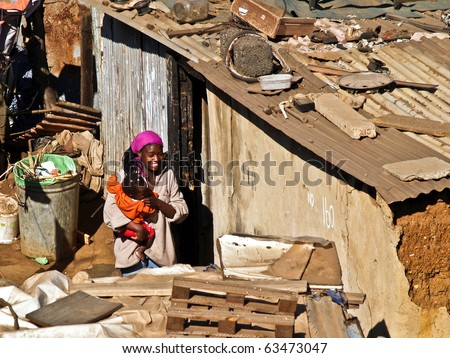 JOHANNESBURG, SOUTH AFRICA - AUGUST 15: Unidentified woman and child in squatter camp on August 15, 2007, in Soweto, Johannesburg, South Africa. Woman holds small child in arms amidst the camp shacks.