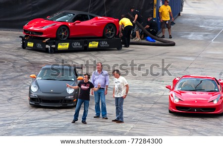 """JOHANNESBURG, SOUTH AFRICA- MARCH 20: Jeremy Clarkson, Richard Hammond and James May from the BBC TopGear show arrive at the Topgear Festival at Kyalami in the """"Thunderdome"""" show on March 20, 2011 in Johannesburg, South Africa. - stock photo"""