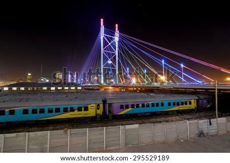 Johannesburg, South Africa - September 3, 2012: Nelson Mandela Bridge at night. The 284 meter long Nelson Mandela Bridge, which crosses over the 40 railway lines that lie spread beneath its span. - stock photo