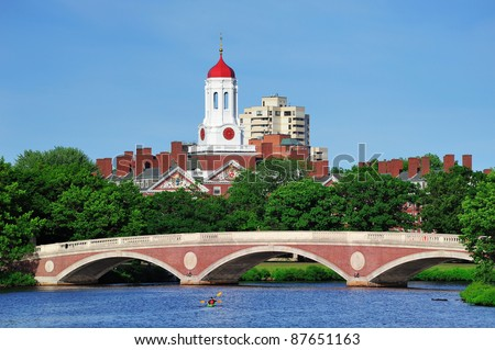 John W. Weeks Bridge and clock tower over Charles River in Harvard University campus in Boston with trees, boat and blue sky. - stock photo