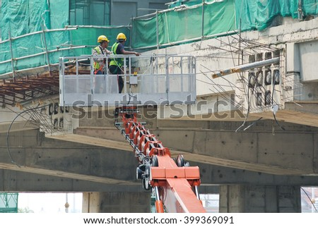 JOHOR, MALAYSIA -JANUARY 20, 2016: Construction workers standing in the mobile crane basket while working at high level in the construction site in Malaysia.