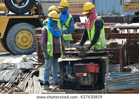 JOHOR, MALAYSIA -JUNE 05, 2016: Construction workers working at the steel bar bending yard in the construction site.