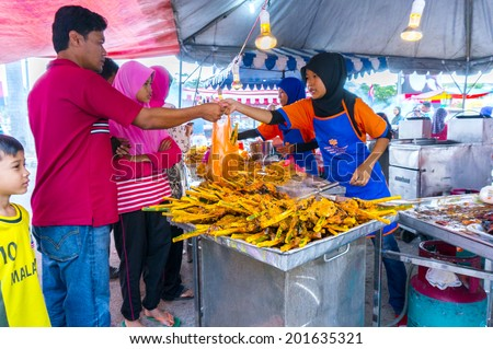 JOHOR, MALAYSIA-JUNE 29: Unidentified traditional roast chicken attends to a customer at Pasar Ramadhan Bukit Gambir on June 29, 2014 in Johor, Malaysia. Muslims around the world start fasting today. - stock photo
