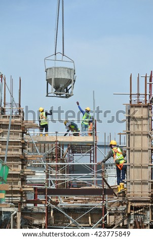 JOHOR, MALAYSIA -MAY 12, 2016: A group of construction workers pouring concrete using concrete bucket into the column form work at the construction site.