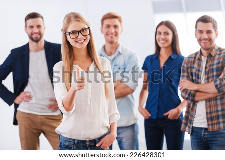 Join a successful team! Beautiful young woman showing her thumb up and smiling while group of happy young people standing on background and smiling - stock photo
