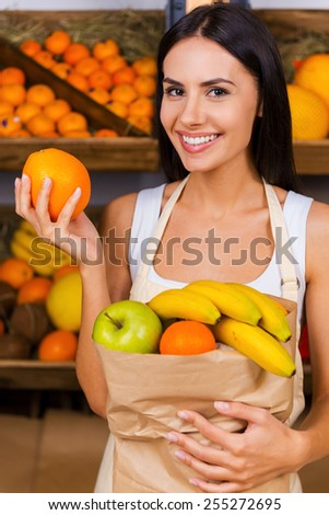 Join healthy lifestyle. Beautiful young woman in apron holding paper shopping bag with fruits and smiling while standing in grocery store with variety of fruits in the background