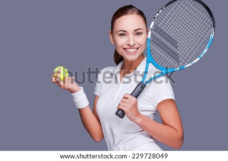 Join me for tennis?  Beautiful young women in sports clothes holding tennis racket on her shoulder and smiling while standing against grey background