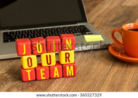 Join Our Team written on a wooden cube in a office desk - stock photo