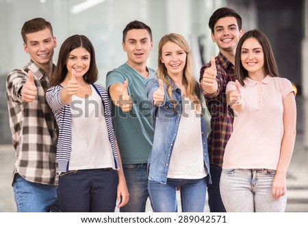 Join successful team! Group of happy young people standing and  showing thumbs up. - stock photo