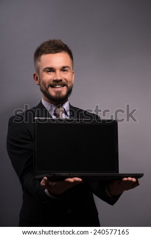Join the digital age. Image of young cheerful businessman in formalwear showing a screen of his laptop and smiling at camera while standing against grey background - stock photo