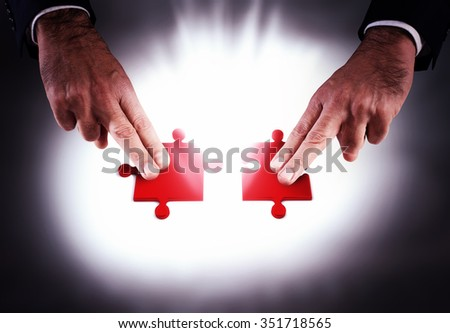 Join two red pieces of a puzzle - stock photo