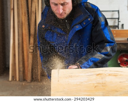 Joiner is cutting tree trunk with chainsaw. He is wearing soundproofing headsets - stock photo