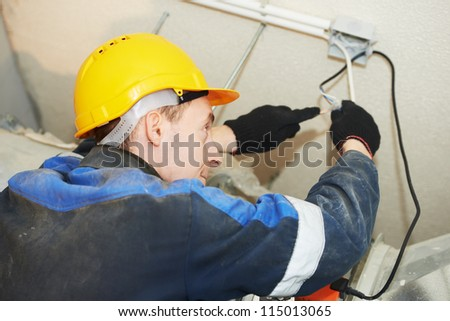 Joiner makes fire safety works on smoke removal system sensor installation - stock photo