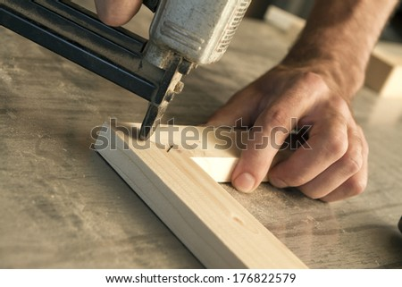 joinery uses a nail gun to attach pieces of wood - stock photo