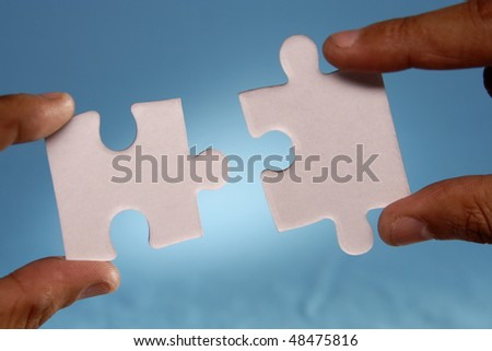 Joining two Jigsaw puzzle pieces - stock photo