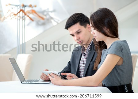 Joint case. Young couple successful businessmen sitting at a table. Man and woman working at a laptop. - stock photo