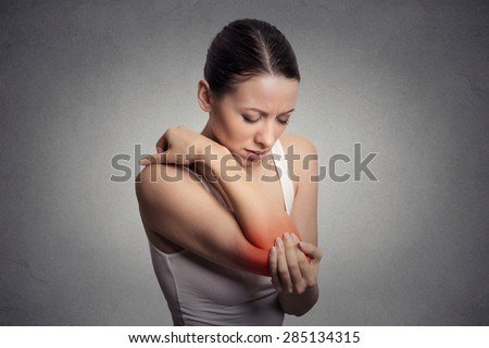 Joint inflammation indicated with red spot on female's elbow. Arm pain and injury concept. Closeup portrait woman with painful elbow on gray background  - stock photo