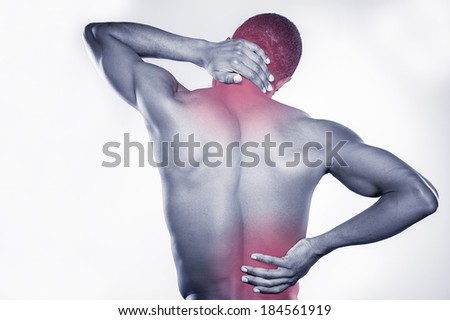 Joint pain. Rear view of young muscular African man touching his neck and hip while standing against grey background - stock photo