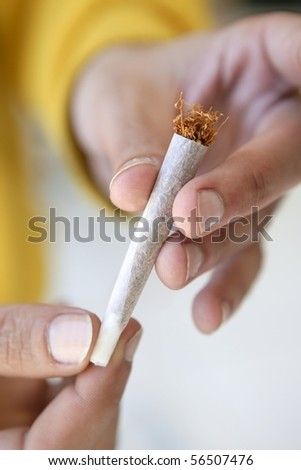 joint tobacco cigarette in hands prepared to smoke - stock photo