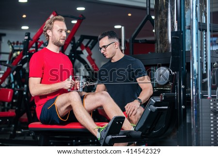 Joint training in the gym with trainer. Confident coach shows the customer how to do the training in the gym on the simulator. - stock photo