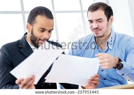 Joint venture. Cheerful businesswoman holding documents in the hands while two successful businessman sitting at the table in a business office in formal wear and work at a laptop. - stock photo