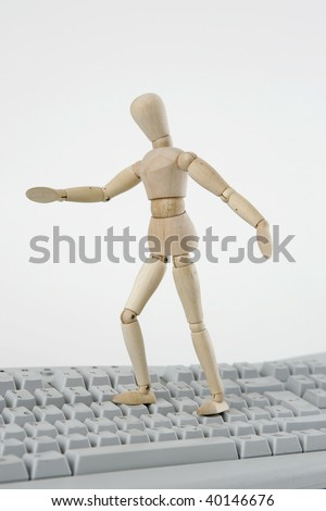 Jointed doll standing on computer keyboard, isolated on white background - stock photo